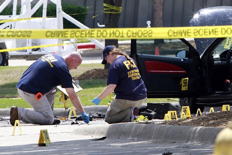 Investigators work a crime scene outside of the Curtis Culwell Center (AFP Photo/Ben Torres)