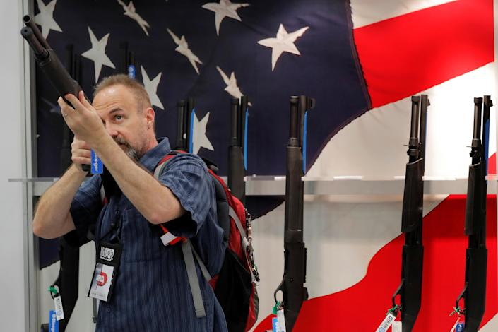 A gun enthusiast looks at a shotgun during the annual National Rifle Association (NRA) convention in Dallas, Texas, U.S., May 5, 2018: REUTERS