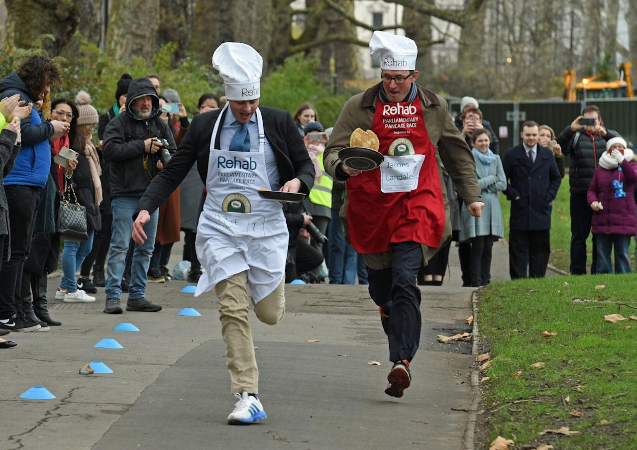 <p>Matt Warman MP (left) and BBC News correspondent James Landale taking part in the Parliamentary Pancake Race in aid of the Rehab disability charity, at Victoria Tower Gardens in Westminster, London. (Kirsty O'Connor/PA Wire) </p>