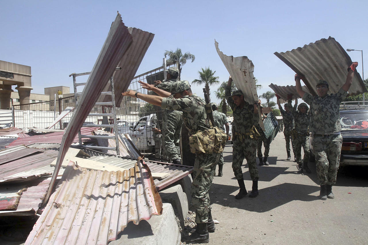 Egyptian Army soldiers clear away scrap metal used by protesters during clashes outside the Ministry of Defense in Cairo, Egypt, Saturday, May 5, 2012. Lawyers say authorities have detained over 300 Egyptian protesters including 18 women following clashes outside the country's Defense Ministry, accused of attacking troops and disrupting public order.(AP Photo/Mahmoud Abd Al-Aziz)