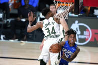 Orlando Magic's Markelle Fultz (20) is fouled by Milwaukee Bucks' Giannis Antetokounmpo (34) during the second half of an NBA basketball first round playoff game Saturday, Aug. 29, 2020, in Lake Buena Vista, Fla. (AP Photo/Ashley Landis)