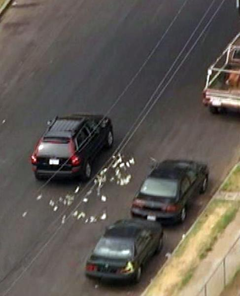 This image provided by KNBC-TV shows bank robbery suspects throwing money from their vehicle during a police pursuit Wednesday Sept. 12, 2012 in Los Angeles. The vehicle was eventually blocked by another vehicle and the suspects were arrested. (AP Photo/KNBC-TV) MANDATORY CREDIT: KNBC-TV
