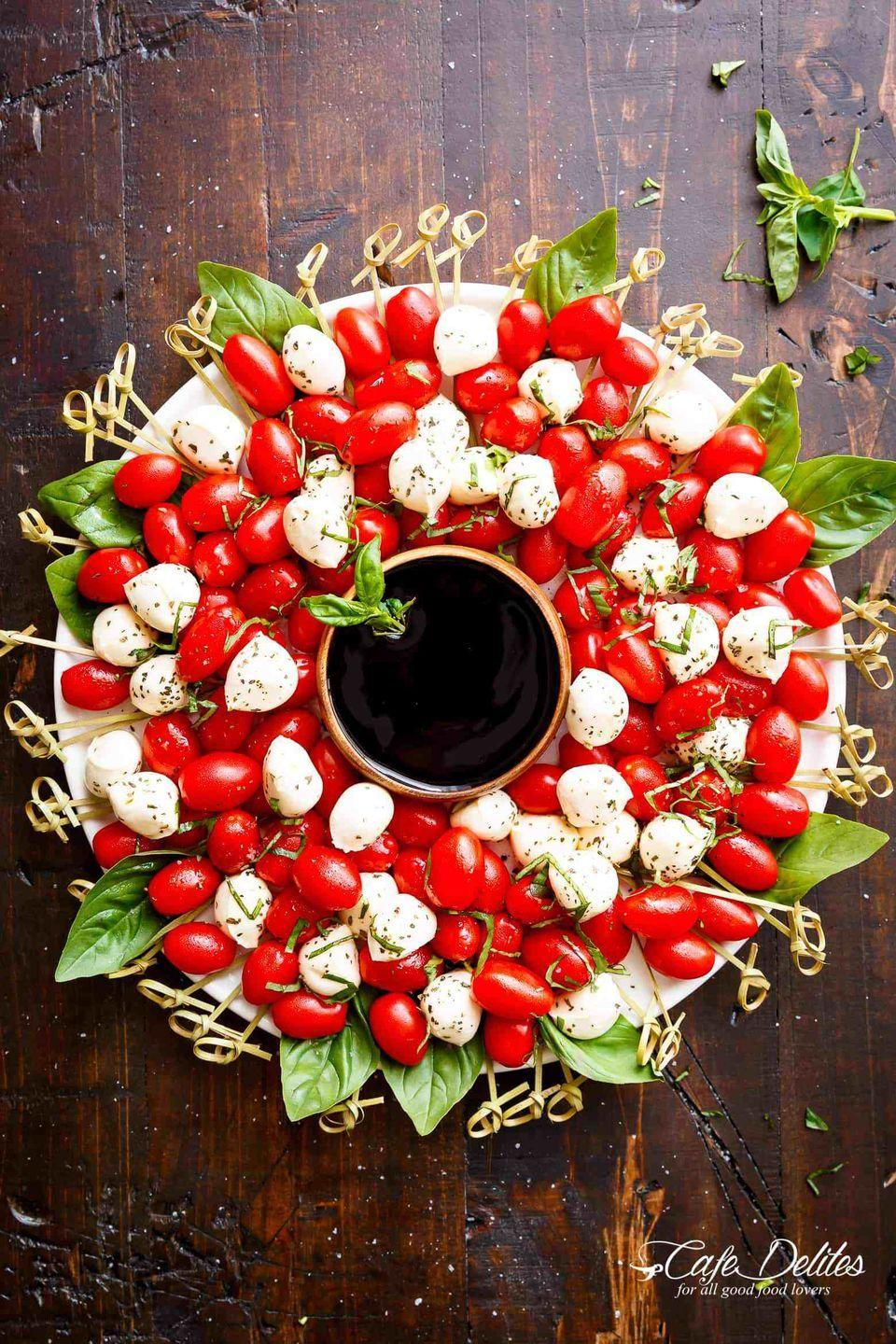 """<p>Mimic your own <a href=""""https://www.countryliving.com/diy-crafts/how-to/g1056/diy-wreath-ideas/"""" rel=""""nofollow noopener"""" target=""""_blank"""" data-ylk=""""slk:Christmas wreath"""" class=""""link rapid-noclick-resp"""">Christmas wreath</a> to make this stunning caprese plate.</p><p><strong>Get the recipe at <a href=""""https://cafedelites.com/caprese-christmas-wreath/"""" rel=""""nofollow noopener"""" target=""""_blank"""" data-ylk=""""slk:Cafe Delites"""" class=""""link rapid-noclick-resp"""">Cafe Delites</a>.</strong></p>"""