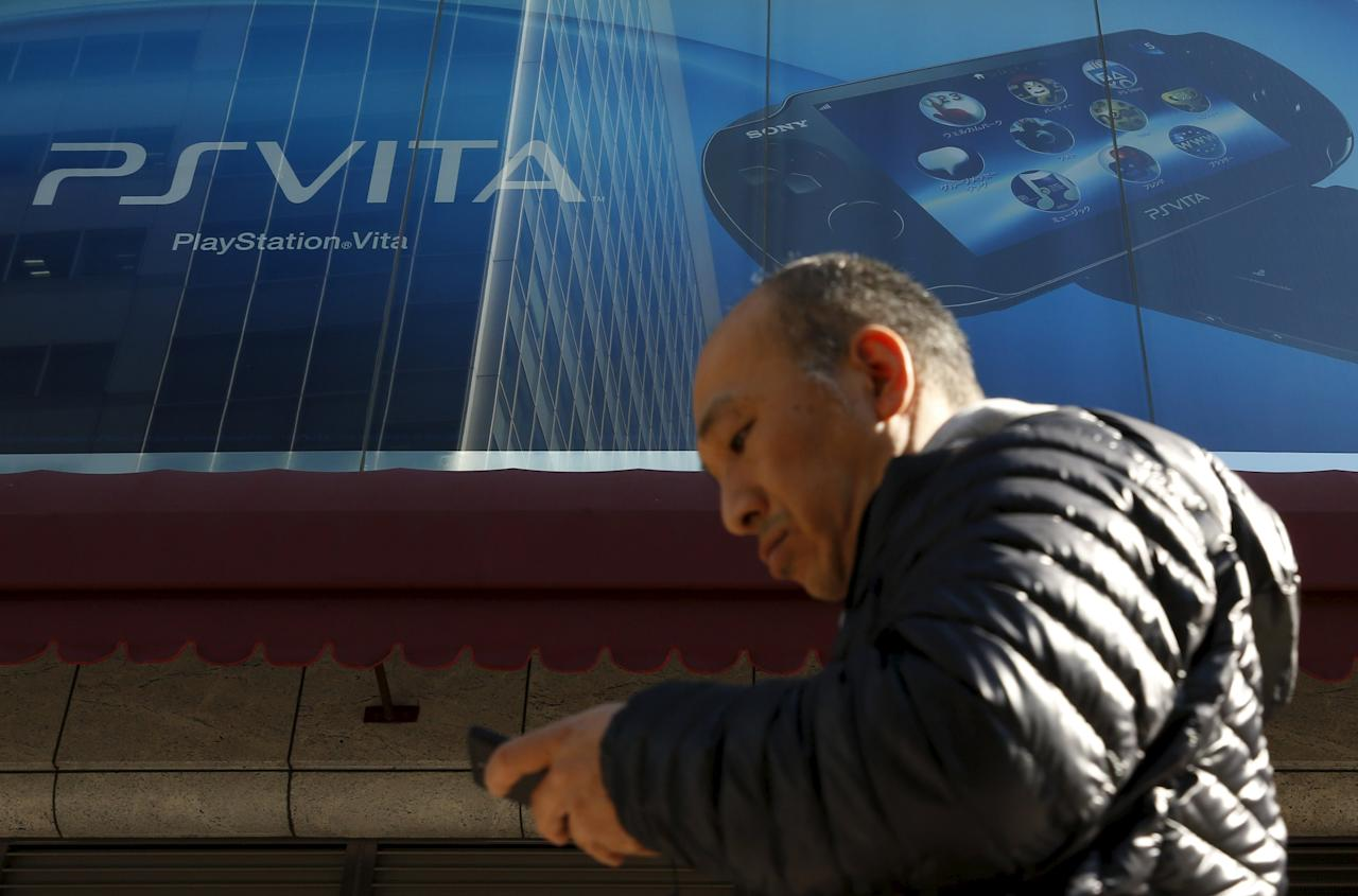 A man using his mobile phone walks under an advertisement board of Sony Corp's PlayStation Vita outside an electronics retail store in Tokyo