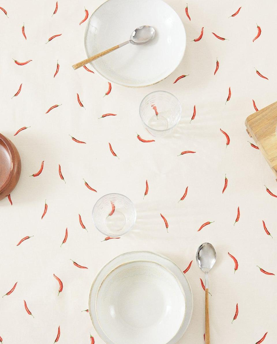 """<p><strong>Zara Home</strong></p><p><strong>$29.90</strong></p><p><a href=""""https://www.zarahome.com/us/new-in/collection/resin-coated-tablecloth-with-chilli-design-c1020381012p302347440.html"""" rel=""""nofollow noopener"""" target=""""_blank"""" data-ylk=""""slk:Shop Now"""" class=""""link rapid-noclick-resp"""">Shop Now</a></p><p>Looking for a different kind of spice? Bring the heat with a chili-dressed table.</p>"""
