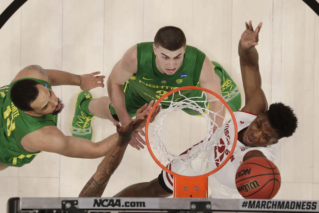 Wisconsin guard Khalil Iverson, right, shoots against Oregon forward Paul White, left, and guard Payton Pritchard during the first half of a first round men's college basketball game in the NCAA Tournament, Friday, March 22, 2019, in San Jose, Calif. (AP Photo/Ben Margot)