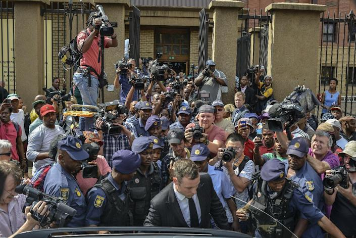 South African Paralympic athlete Oscar Pistorius (front), surrounded by policemen, journalists and onlookers, leaves the Pretoria Hight Court following his sentencing hearing on October 13, 2014 (AFP Photo/Mujahid Safodien)