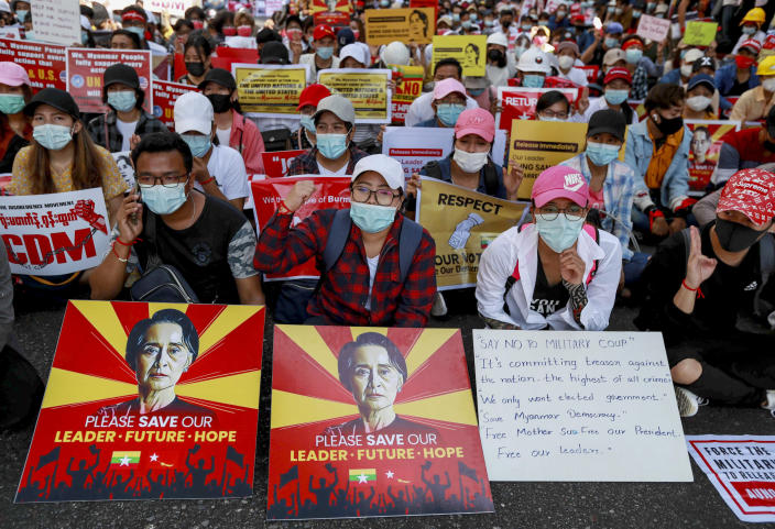 """Demonstrators display placards with pictures of deposed Myanmar leader Aung San Suu Kyi and a sign that shows CDM, promoting """"Civil Disobedience Movement"""" to protest against the military coup in Yangon, Myanmar, Wednesday, Feb. 17, 2021. The U.N. expert on human rights in Myanmar warned of the prospect for major violence as demonstrators gather again Wednesday to protest the military's seizure of power. (AP Photo)"""