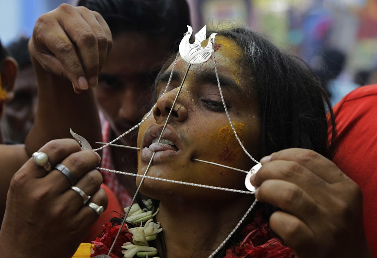 <p>A Hindu devotee, has her tongue and cheeks pierced with metal rods as part of a ritual during a religious procession dedicated to Hindu goddess Mutthumariamman in Bandel, about 60 kilometers (38 miles) north of Kolkata, India, Wednesday, April 5, 2017. The ritualistic acts of inflicting pain on oneself are performed as an act of penance with the belief that it will prevent diseases and provide the well-being of the families of devotees. (AP Photo/Bikas Das) </p>