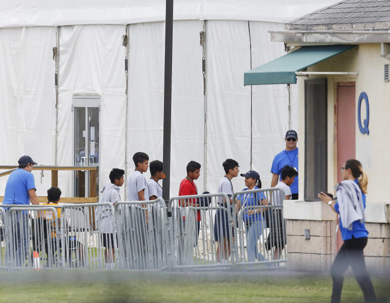 FILE - In this June 20, 2018 photo, immigrant children walk in a line outside the Homestead Temporary Shelter for Unaccompanied Children a former Job Corps site that now houses them in Homestead, Fla.  Migrant children who were separated from their parents at the U.S.-Mexico border last year suffered post-traumatic stress and other serious mental health problems, according to a government watchdog report obtained by The Associated Press Wednesday. The chaotic reunification process only added to their trauma. (AP Photo/Brynn Anderson, File)