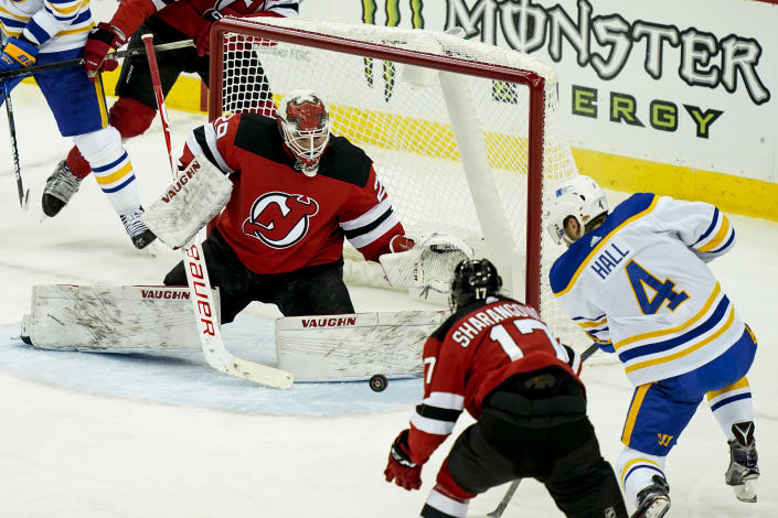 Buffalo Sabres left wing Taylor Hall (4) takes a shot on New Jersey Devils goaltender Mackenzie Blackwood (29) during the first period of an NHL hockey game, Saturday, Feb. 20, 2021, in Newark, N.J. (AP Photo/John Minchillo)