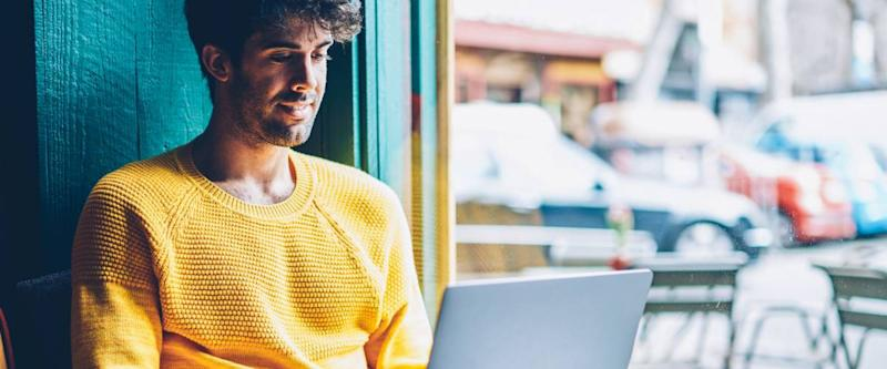 Smiling hipster guy applying for debt consolidation loan online