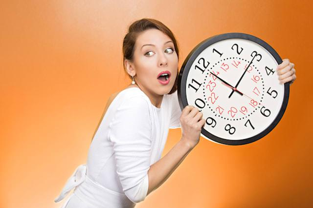 Closeup portrait woman, worker, holding clock looking anxiously, pressured by lack, running out of time, isolated orange backgro