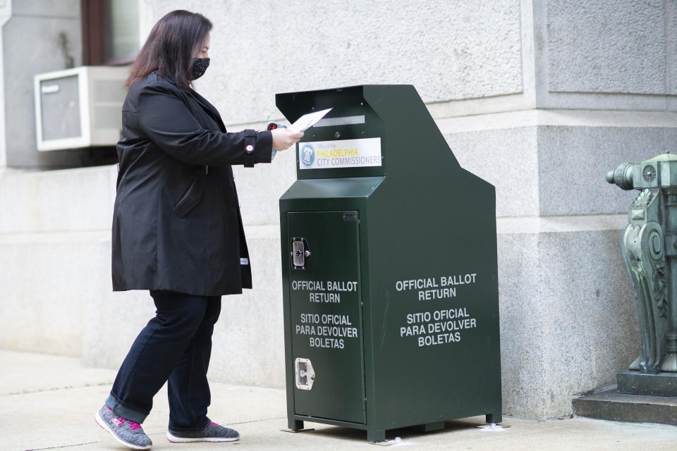 A voter casts her early voting ballot at drop box outside of City Hall on October 17, 2020 in Philadelphia, Pennsylvania. (Mark Makela/Getty Images)