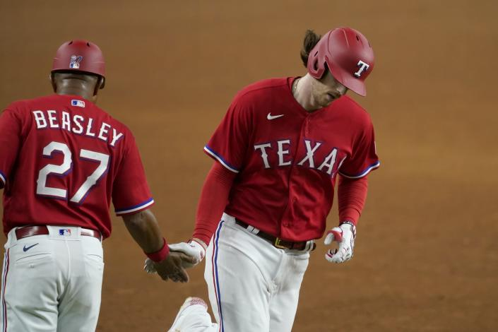 Texas Rangers third base coach Tony Beasley (27) congratulates Jonah Heim on his solo home run in the sixth inning of a baseball game against the Seattle Mariners in Arlington, Texas, Friday, July 30, 2021. (AP Photo/Tony Gutierrez)