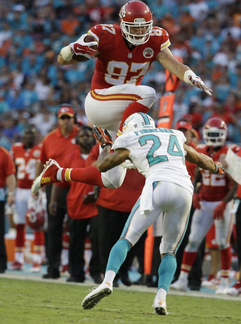 Kansas City Chiefs tight end Travis Kelce (87) jumps to avoid a tackle by Miami Dolphins cornerback Cortland Finnegan (24) during the second half of an NFL football game, Sunday, Sept. 21, 2014, in Miami Gardens, Fla. (AP Photo/Lynne Sladky)