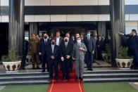 Libya's Prime Minister Abdulhamid Dbeibeh, Libya's internationally recognized former Prime Minister Fayez al-Sarraj, and Mohammed al-Menfi, Head of the Presidency Council, pose for a photo after the handover ceremony in Tripoli