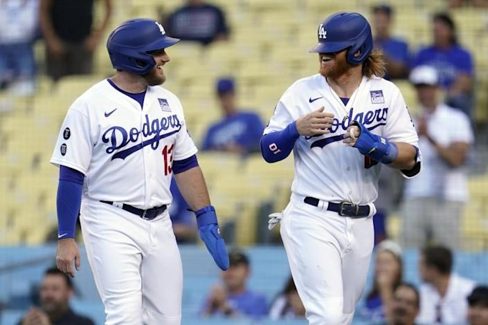 Los Angeles Dodgers' Justin Turner, right, smiles with Max Muncy after they scored on a single by Cody Bellinger during the first inning of the team's baseball game against the St. Louis Cardinals on Wednesday, June 2, 2021, in Los Angeles. (AP Photo/Marcio Jose Sanchez)