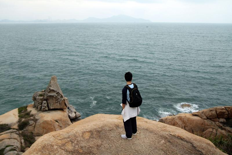 This April 2010 photo courtesy of Suzanne Ma shows a visitor looking out at the sprawling green waters of the South China Sea as seen from red, granite cliffs in Cheung Chau, Hong Kong. Just eight miles from Hong Kong's Central Pier, Cheung Chau was once a pirate's cove - a place where renegades of the South China Sea stashed their booty. Today, it is a hideout for tourists and locals alike, and makes for a perfect escape from the big city.    (AP Photo/Suzanne Ma) NO SALES