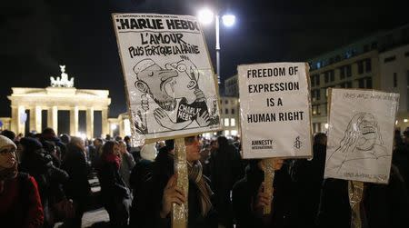People hold placards, one with a copy of weekly satirical magazine Charlie Hebdo, as they pay tribute to victims in front of the Brandenburg Gate (L, background) near the French embassy at Pariser Platz in Berlin January 7, 2015, following a shooting by gunmen at the offices of weekly satirical magazine Charlie Hebdo in Paris. REUTERS/Fabrizio Bensch