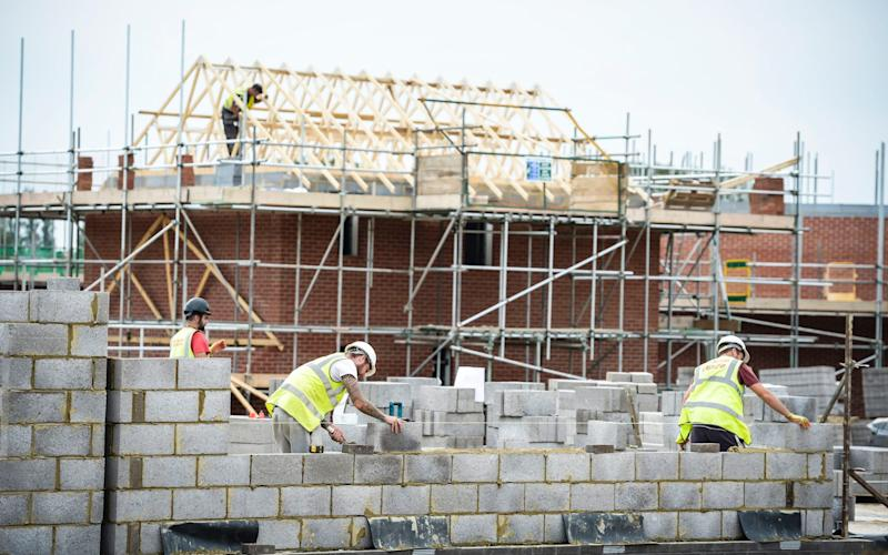 Builders lay blocks on a building site near Bristol - Ben Birchall