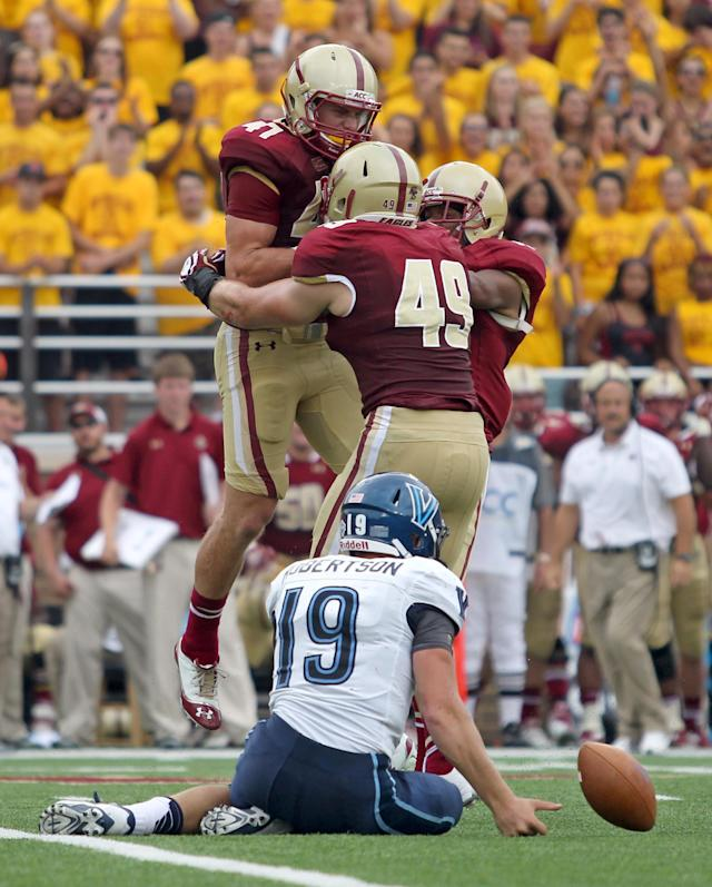 Boston College defensive back Spenser Rositano, left, celebrates with teammates Steele Divitto (49) and Bryce Jones, right, after sacking Villanova quarterback John Robertson during the first half of an NCAA college football game, Saturday, Aug. 31, 2013, in Boston. (AP Photo/Mary Schwalm)