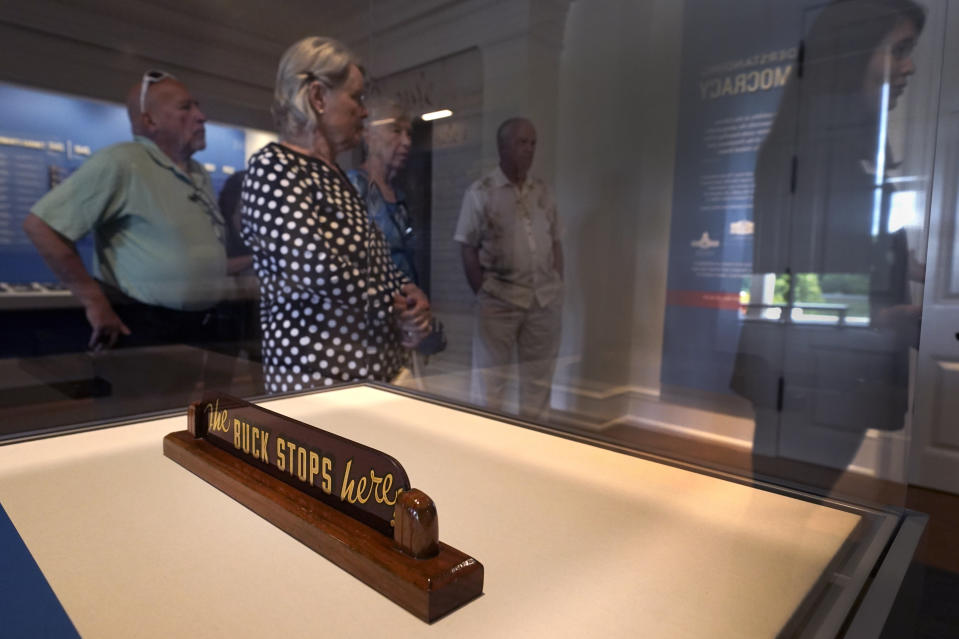 """Visitor's view an exhibit near a sign that reads """"The Buck Stops Here,"""" which once sat on the President Harry S. Truman's desk at the Harry S. Truman Presidential Library and Museum Wednesday, June 9, 2021, in Independence, Mo. The facility will reopen July 2 after a nearly $30 million renovation project. (AP Photo/Charlie Riedel)"""
