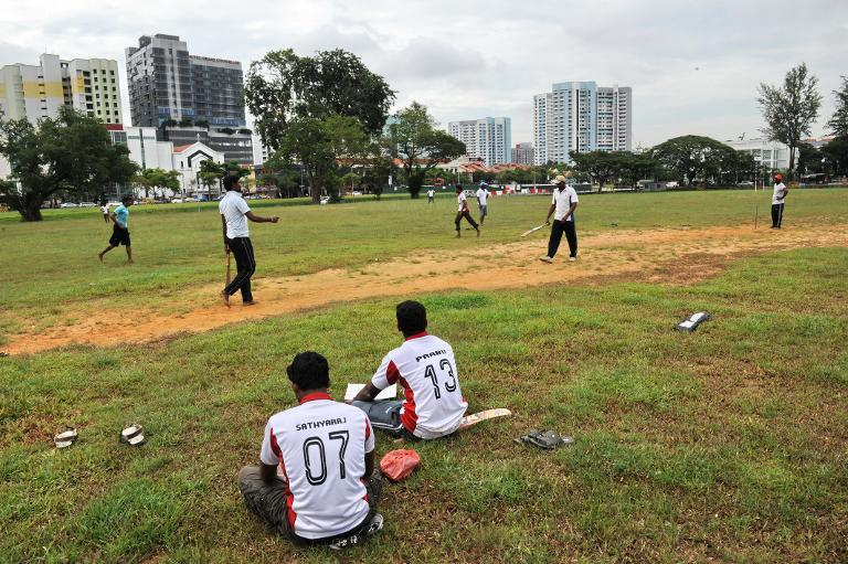 South Asian workers play a cricket game on the field next to Little India district in Singapore on December 15, 2013