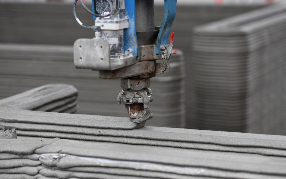 The head of a 3D printer applies the next layer of concrete to the walls of a house at the construction site in Beckum, western Germany, on November 26, 2020. - According to North Rhine-Westphalia's state government, Germany's first residential building constructed by 3D printing or additive manufacturing technique is currently being built in Beckum. (Photo by Ina FASSBENDER / AFP) (Photo by INA FASSBENDER/AFP via Getty Images)