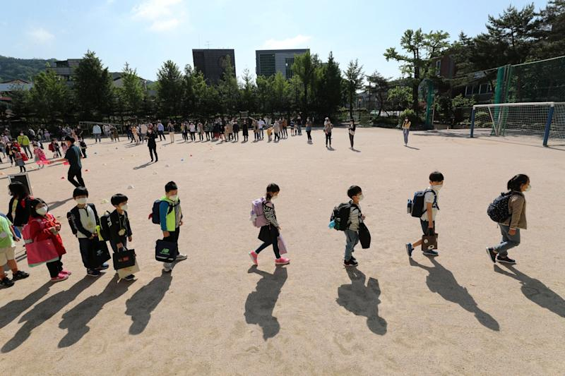 Students arrive at an elementary school in Seoul on Wednesday (REUTERS)