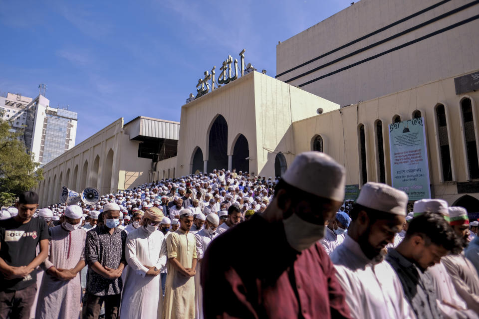 Supporters of several Islamist parties offer prayers in front of the main Baitul Mokarram national mosque in Dhaka, Bangladesh, Friday, Oct. 30, 2020. After weekly Friday prayers, thousands of Muslims and activists marched through streets and rallied across Bangladesh's capital on Friday against the French president's support of secular laws that deem caricatures of the Prophet Muhammad as protected under freedom of speech. (AP Photo/Mahmud Hossain Opu)
