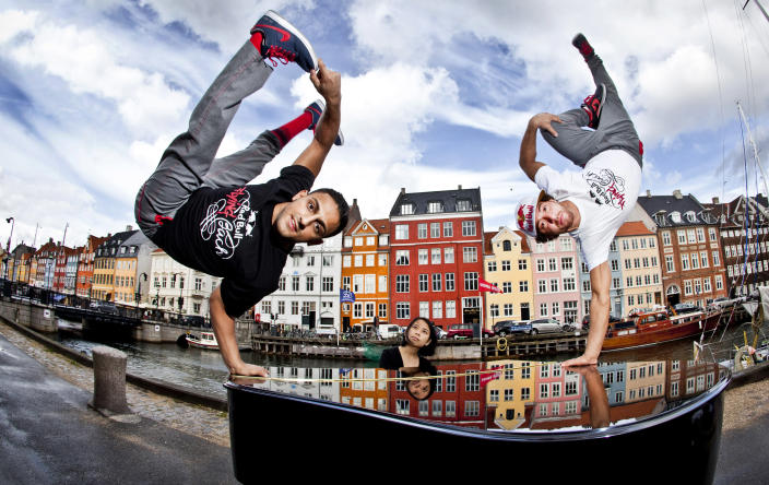 """In this handout image provided by Red Bull, Gengis """"Lil Ceng"""" Ademoski (L) and Khaled """"KC"""" Chaabi (R) of the four time world champion Berlin dance troupe """"Flying Steps"""" strike a freeze on a piano played by muscian Jia Lim (C) of Singapore at the 17th century waterfront area of Nyhavn in build up to the Red Bull Flying Bach European Tour, a show that features the cultural clash of break dancing with the classical music of Johann Sebastian Bach, on August 30, 2011 in Copenhagen, Denmark. (Photo by Dean Treml/Red Bull via Getty Images)"""