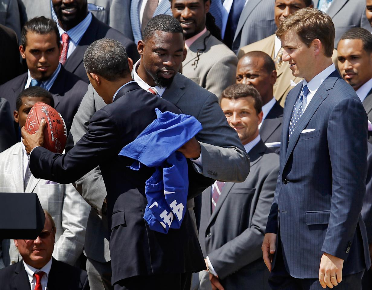 WASHINGTON, DC - JUNE 08:  U.S. President Barack Obama New York Giants player Justin Tuck as quarterback Eli Manning looks on during a ceremony for the National Football League Super Bowl champions at the White House June 8, 2012 in Washington, DC. The Giants defeated The New England Patriots 21-17 to win Super Bowl XXXXVI.  (Photo by Chip Somodevilla/Getty Images)