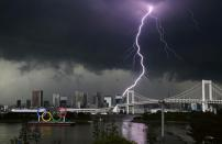 A lightening is seen over the giant Olympic rings and the Rainbow Bridge from the waterfront area in Tokyo