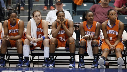 Sam Houston State players watch as Oral Roberts players celebrate winning an NCAA college basketball game for the Southland Conference women's tournament title, Saturday, March 16, 2013, in Katy, Texas. Oral Roberts won 72-66. (AP Photo/David J. Phillip)