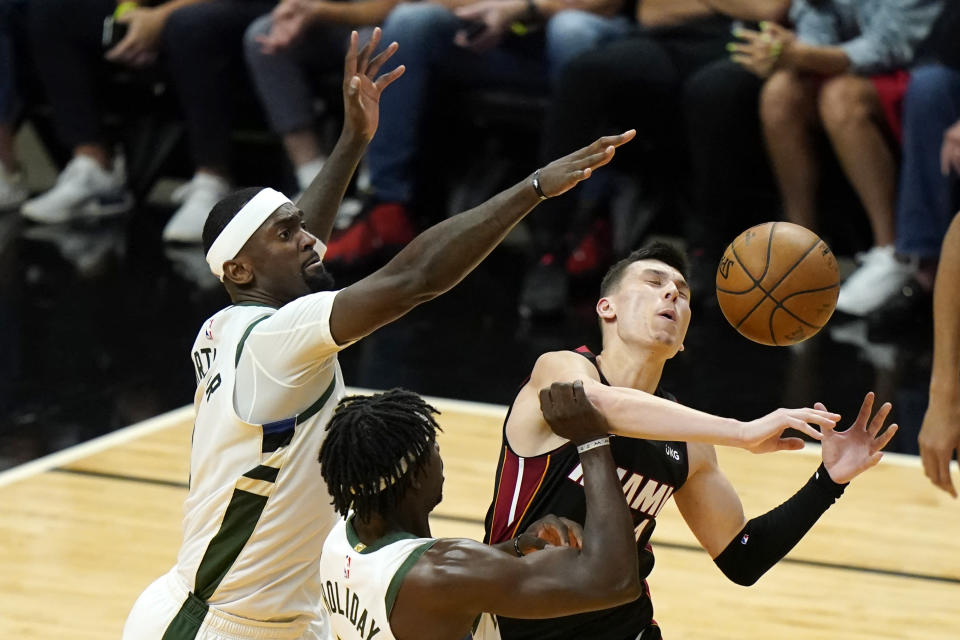 Miami Heat guard Tyler Herro, right, is fouled by Milwaukee Bucks guard Jrue Holiday, center, as center Bobby Portis defends during the second half of Game 4 of an NBA basketball first-round playoff series, Saturday, May 29, 2021, in Miami. (AP Photo/Lynne Sladky)