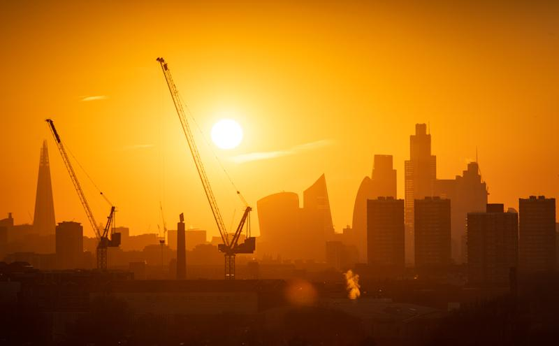 The sun sets behind tower cranes and the London skyline, including the Shard (left) and skyscrapers in the city financial district of London.
