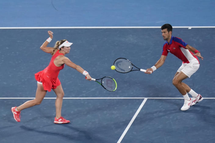 The Serbian mixed doubles team of Nina Stojanovic, left, and Novak Djokovic play during the quarterfinals of the tennis competition at the 2020 Summer Olympics, Thursday, July 29, 2021, in Tokyo, Japan. (AP Photo/Seth Wenig)