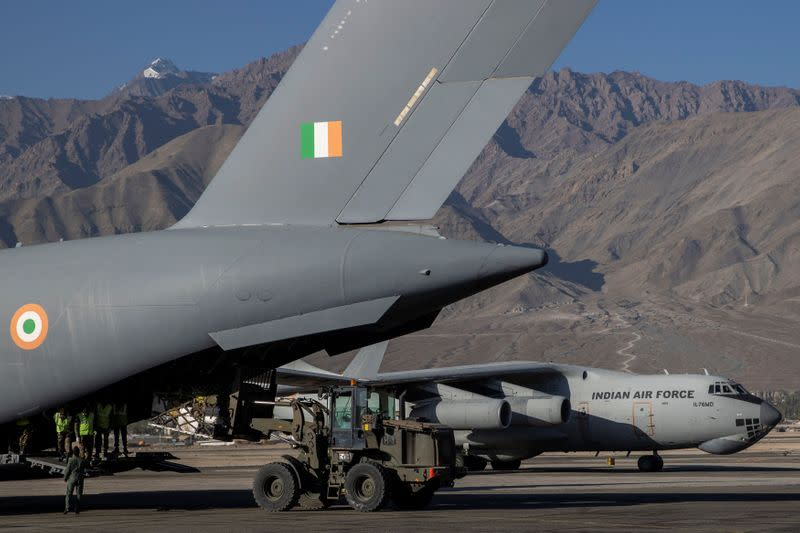 A military transport plane taxis as another unloads supplies at a forward airbase in Leh