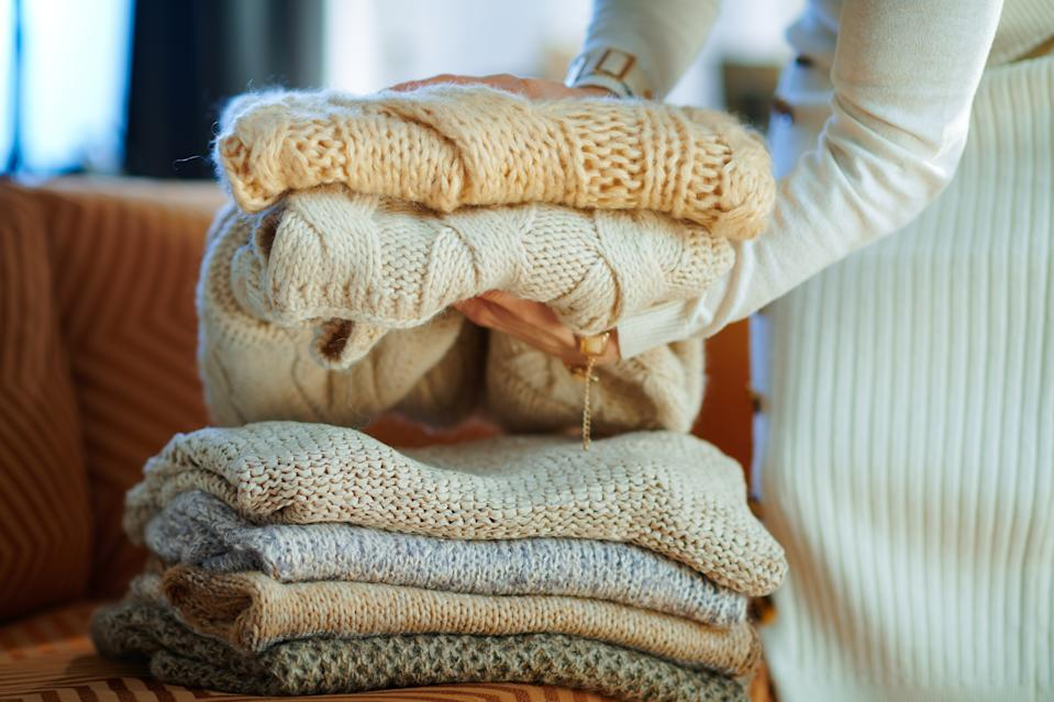 Closeup on stylish woman in white sweater and skirt in the modern living room in sunny winter day near couch folding sweaters for storage.