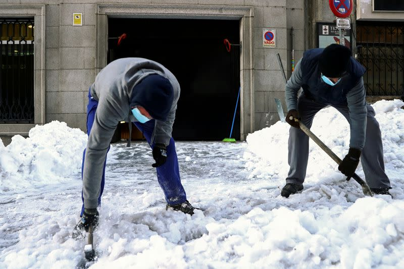 FILE PHOTO: Workers use a hammer and a shovel to break ice, in Madrid