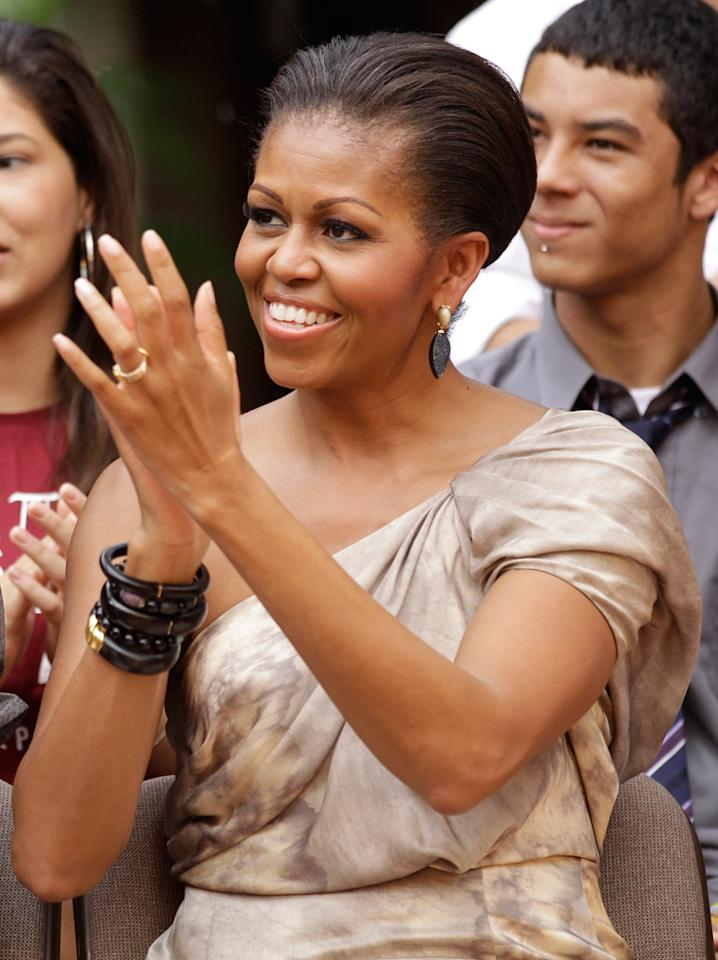 Photo by: (AP Photo/Silvia Izquierdo)<br />Michelle Obama attends cultural performances in Brasilia, Brazil, March 19, 2011.-<br />U.S. first lady Michelle Obama applauds as she attends cultural performances at Oca da Tribo restaurant in Brasilia, Brazil, Saturday March 19, 2011. Michelle Obama and her two daughters Sasha and Malia attended cultural performances with young Brazilians, many from disadvantaged backgrounds who have participated in a range of U.S. sponsored exchange and leadership development programs.