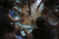 People prepare dozens of momos, traditional Tibetan steamed dumplings, in the garage of a home in Columbia Heights, Minn., on Monday, July 19, 2021. (AP Photo/Jessie Wardarski)