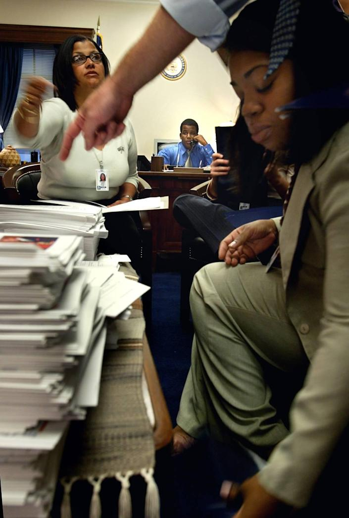 In September 2003, new immigration member Kendrick Meek spoke on the phone while preparing breakfast, which was being hosted as part of the Congressional Black Caucus. Staff Shirley Lafrul (right) and Regina Romero put together the folders for Chief of Staff John Shelble to point and direct.