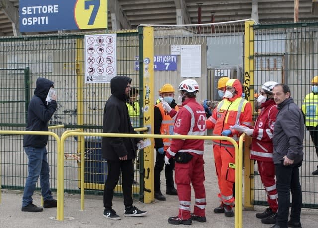 Spectators have their temperature measured as they enter the Via Del Mare Stadium in Lecce