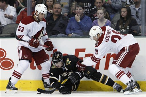 Phoenix Coyotes defenseman Derek Morris (53) watches as left wing Lauri Korpikoski (28), of Finland, attempts to gain control of the puck from Dallas Stars' Stephane Robida,s who lost his stick earlier in the play during the second period of an NHL hockey game Tuesday, March 20, 2012, in Dallas. (AP Photo/Tony Gutierrez)