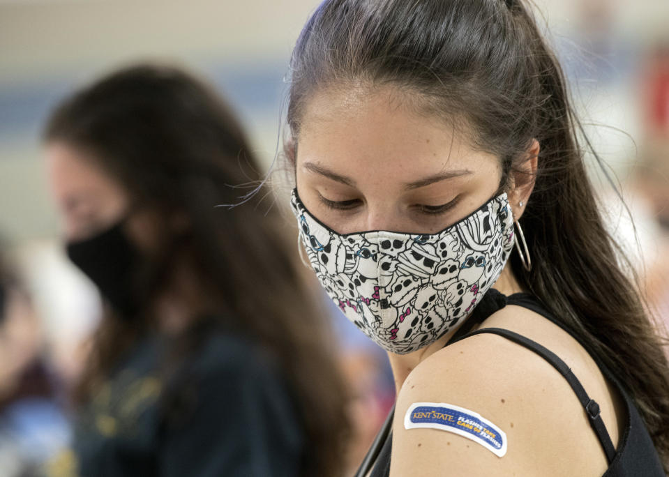FILE - In this Thursday, April 8, 2021, file photo, Kent State University student Regan Raeth, of Hudson, Ohio, looks at her vaccination bandage as she waits for 15 minutes after her shot in Kent, Ohio. On Wednesday, May 12, 2021, Gov. Mike DeWine announced the end of the state's mask mandate as new COVID-19 cases decrease and more Ohioans get vaccinated. DeWine said the mask mandate will end June 2 except for nursing homes and assisted living facilities. (AP Photo/Phil Long, File)