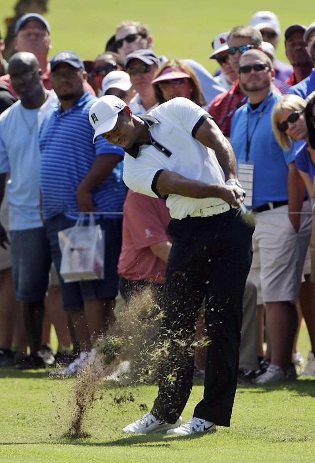 Tiger Woods hits from the rough on the first fairway during the second round of the Tour Championship golf tournament at East Lake Golf Club in Atlanta, Friday, Sept. 20, 2013. (AP Photo/John Bazemore)