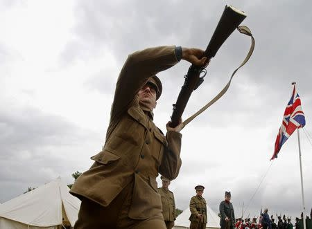 Custom silicone technician Corin Watts, portraying a Lance Corporal in the Kings Royal Rifle Corps, part of the Rifles Living History Society, participates in a rifle drill whilst recreating life as a First World War soldier at the Colchester Military Tournament in Colchester, eastern England July 6, 2014. REUTERS/Luke MacGregor