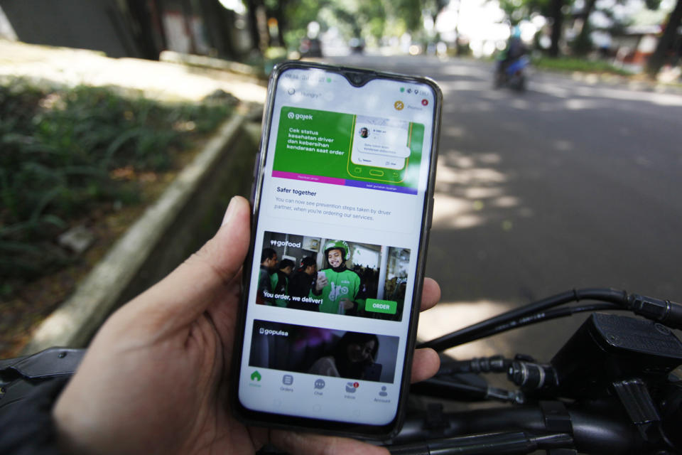 A Man use his a mobile phone, using Gojek app at a street in Bogor, Indonesia. June 9, 2020. Facebook Inc messaging platform WhatsApp and PayPal Holdings Inc have invested in payment, food delivery, and ride-hailing app operator Gojek. According to a regulatory filing, Facebook now owns a 2.4 percent stake in Gojek's GoPay fintech arm, while PayPal owns 0.6 percent of GoPay (Photo Illustration by Adriana Adie/NurPhoto via Getty Images)